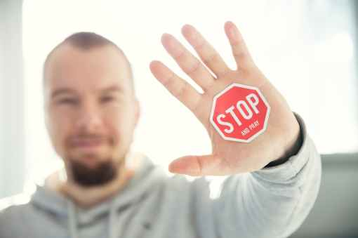 photography of a persons hand with stop signage